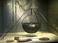 A cauldron with a bird-footed tripod and various cooking implements.