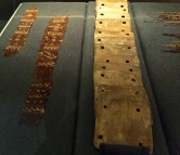 A tablet loom (right) for weaving ribbons like those seen on the left.