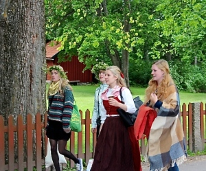 Swedish maidens wearing fancy floral crowns head out to celebrate Midommar.