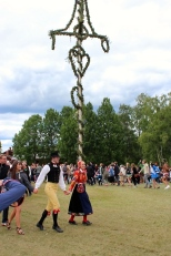 People dressed in traditional Swedish outfits lead the dancing.