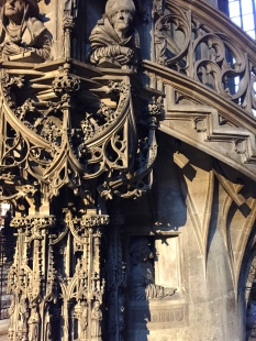 "The stone pulpit sinuously entwines itself around a column. Depicted are four church fathers of the faith being gawked at by the sculptor himself. (You can barely see him craning his neck out of a window beneath the stairs. In German he's called the Fenstergucker -- ""window gawker."")"