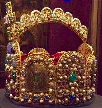 """Charlemagne's Crown"" has eight sides symbolizing the eight gates to Jerusalem. Seed pearls on this side of the arch read: Romanoru (M) Imperator Aug(ustus), ""Emperor of the Romans (and) Augustus."" On the other side it says: Chuonradus Dei Gratia"" Conrad, by the Grace of God."" (Conrad was the ruler after Otto.) The little cloisonné guy is King Solomon, who symbolizes royal wisdom."