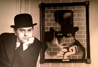 René Magritte poses next to his self-portrait.