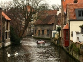"""Bruges was once called the """"Venice of the North"""" for its lovely canals. Note the swans -- the symbol of Bruges. Legend has it that a famously long-necked, 15th-century mayor collaborated with the Austrians and was beheaded by the townspeople for his betrayal. The angry Austrians cursed Bruges and said that similarly long-necked swans would forever haunt its canals to remind its citizens of the murder."""