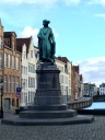 The statue is of Jan Van Eyck, the famous Flemish Primitives painter who spent the last decade of his life working in Bruges. (He's actually Dutch by birth.)