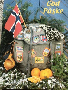 "I love this Easter postcard, which wishes the recipient ""Good Pasque."" It shows how a good Norwegian celebrates the season. The knapsack contains patches showing the requisite hikes around the country, classic knitted Norwegian gloves, oranges, and a wooden birch cup for getting water out of mountain streams."