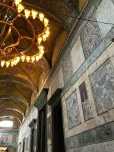 The Imperial Gate (center) leads into the central nave. The walls in this vestibule are lined with inch-think, book-matched marble panels. The ceiling above displays original, 6th-century mosaics. Since these designs are geometric, they were left intact by Christian Iconoclasts (8th Century) and Ottomans (15th Century), both of whom believed representations of people in a church or mosque were idolatrous.