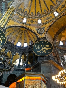 Eight enormous calligraphic medallions hang from the base of the various apse arches. At 24 feet in diameter, they're said to be the largest Islamic calligraphic art in the world. The one you see here bears the name of Muhammed, while the others are painted with the names of Allah and leading figures in Islam. The intricate gilded cage beneath the medallion is the Sultan's loge, his personal prayer platform.