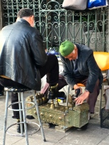 The sidewalks abound with shoeshine men bowing before their ornate brass kits.
