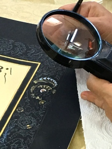 Another teacher shows us how she uses a magnifying glass to paint Tezhip illuminations on manuscripts, scrolls, and books. In this case, she's creating a border for a matt that surrounds a verse of the Quran.