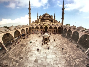 """Matthew snapped a photo of this mural that shows the inner courtyard of the Blue Mosque. In the center is an old fountain once used for ablutions (ritual washing) before prayer. New washing stations sit along the wall at the entry to this courtyard to accommodate more people. When the mosque itself fills up on special holy days, the overflow population prays here in the inner courtyard. I guess Muslims have their equivalent of """"Chreasters,"""" too (Christians who attend services only on holidays like Christmas and Easter)."""