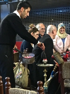 The waiter refills the neighboring table's hookah with fresh wood coals. The family in the background is the one that shared their birthday cake with us.