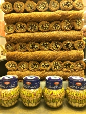 """Nuts preserved in jars of honey compete with a tower of """"kadayif,"""" a dessert made of shredded wheat, nuts, and syrup."""