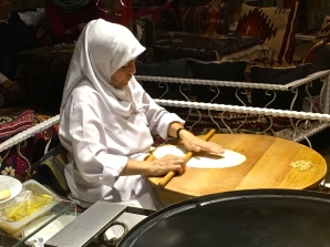 """A woman rolls out dough for """"gozleme,"""" a type of flatbread cooked on the convex metal oven nearby her."""
