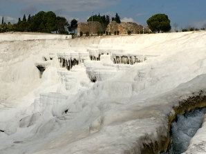Geothermal pools are telltale signs of underground volcanic activity. Many earthquakes have hit Hieropolis over the years; the last one leaving it in ruins in 1354 A.D. In this photo, some of the city's remains can be seen above the travertine terraces.