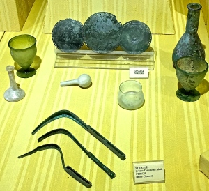 Typical Roman bathing gear included mirrors (the round discs) and strigils (the curved blades -- these are used to scrape off sweat and oil from bathers.)