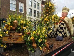 A bakery chain advertises with their float made of flowers and bulbs (look closely at the stem crossing in front of the baker.)