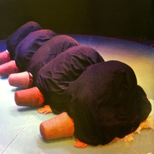 """Dervishes begin the performance wearing hats called """"sikke"""" that represent tombstones and black coats called """"hirka"""" that symbolize the tomb. The Dervishes prostrate themselves, pleading for death of the ego."""