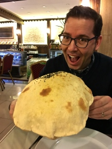 "Matthew prepares to collapse a freshly-baked puffed ""lavash."""