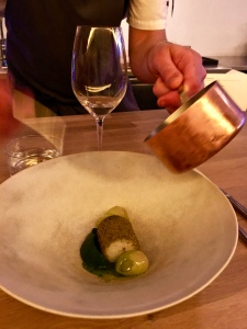 Much of the meal proceeded like performance art, with the chef applying the finish touches by hand, as with the dish of pollack, ramson, and spruce here.
