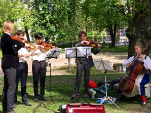 Here, a group of school kids raises money for their school orchestra by performing in the park.