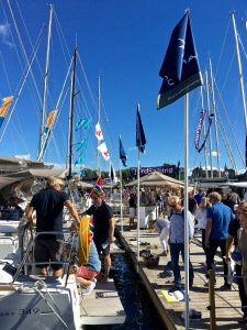 Check out the lineup of folks waiting to board the gorgeous sailboats on show.