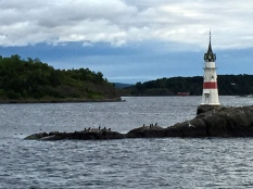 "Pictured is the tiny Kavringen Fyr at Hovedøya, the big island across from City Hall. Not really a true lighthouse, it's only about the size of a miniature golf obstacle. The other tiny lighthouse has a more appropriate name: Kobbernaglen Lykt, which means ""Copper Rivet Lantern."""