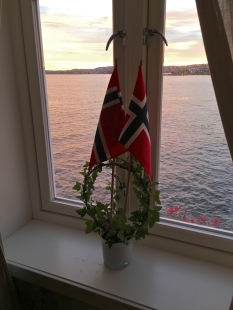Another peaceful view, this one is adorned with the requisite Norwegian flags and a living ivy wreath. Such wreaths seems to be a popular window dressing in many Norwegian homes. I got one myself recently, but I haven't figured out how to keep the spider mites off of it.