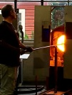 "Glass that has cooled to the correct orange-red stage for blowing gets placed into a smaller oven called the ""Glory Hole."" The glassblower first heats the end of the blowpipe, then dips it into the molten puddle of glass to collect a blob called a ""gather."" He then rolls the gather of glass on a steel plate called a ""marver"" (notice the slab of metal beneath his hands.) The process of ""marvering"" forms a cooled skin on the exterior surface of the glass so that it will more easily hold its shape as the glassblower works with it."