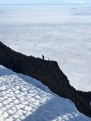 A brave lone hiker teeters on a ridge sandwiched between a snow field and a cloud bank.