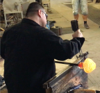 The glassblower then uses a jack to help shape the piece, giving it a neck. The jack will also be used to open the neck wider, so that the piece will become a vase.