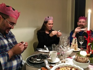 "The almond-flavored Kransekake (""wreath cake"") comes with candies and British crackers pinned to it. So we played the traditional game of snapping open the crackers with a communal tug, then donning the crowns and reading the jokes hidden inside. Only one problem. The jokes were in Norwegian, so we had to do some creative translating."