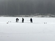 Note that these avid players have brushed away the snow for a smoother hockey-rink surface. Their snow boots act as goal posts at either end.