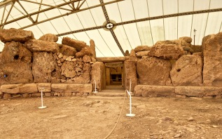 The façade of Mnajdra's South Temple is concave and opens out onto a paved courtyard, just like the temples at Ħaġar Qim. This South Temple also sits on a similar raised foundation that forms a kind of bench. During the spring and autumn equinoxes, the sun blazes a path through the front door and down the corridor until it hits the altar along the back wall of the rear apse.