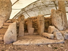 "In this photo of an exterior, open-air chapel or shrine, you can just barely see the ""Solstice Hole"" visible in the earlier photo. It's hidden behind the altar pillar on the right side, towards the bottom. Archaeologists think that, in addition to tracking the solstices, the hole may have been used as an ""oracle mouthpiece"" so that sounds or voices from the interior apse could issue forth mysteriously to the exterior chapel. The triangular altar table you see in the center here is the only one of its kind in all of the Maltese temples."