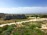 """Look closely at the back wall of the Ġgantija Temple Complex, and you'll see another common temple trait: """"header-and-stretcher"""" construction -- blocks that lie with their long side stretching out along the ground, alternating with blocks that stand upright (called """"orthostats."""") This pattern allows the orthostats to tie in with the rubble behind the wall, strengthening the entire structure without the use of mortar."""