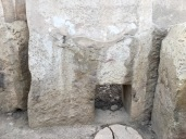 Along the apse that leads from Tarxien South to Tarxien Central, a narrow passage provides entrance into an L-shaped chamber with cruder carvings than found elsewhere in the temple. One megalith holds an image of two bulls facing each other. You can see one here, just above the square opening. Along the floor of this chamber is a round paving stone that can be lifted to access a pit. Maybe a well of some kind?