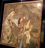 "Notice the tiny ""tesserae"" -- four-sided tiles -- that make up this mosaic. The subject? Two crazy maenads surprising a naked satyr who's sleeping off his liquor. Although it looks pretty violent, it's supposedly a humorous scene from a satyrical play where the ladies playfully attempt to cut off the poor guy's hair and beard. The mosaic originally covered the home's entry vestibule and was intended to impress visitors with the owner's wealth and style."