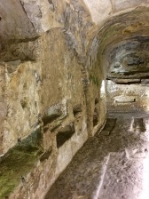 """A variety of nooks along the walls had different purposes. Some were reserved for children, whose bodies were usually cremated. The ashes were then poured into clay jars called amphorae that were tucked into wall niches. Other smaller divots held oil lamps so that families could see well enough to perform last rites. Still other holes acted as """"feeding tubes"""" for the dead. During the """"Last Supper"""" with their loved one, the family would mix together leftover crumbs and wine from the meal and pour it into the hole as a libation/offering to the deceased. Hey, they might get hungry and thirsty on their journey to the Afterlife."""