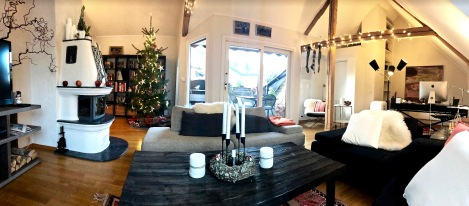 "My sis took this panoramic of the entire living room, complete with decorated tree, tabletop advent wreath, apples on the mantle, and stockings hung by the fireplace and along the rafter. The knitted socks are called ""strømper"" and are from old bunads (national costumes) for men. We got them at Uff, a second-hand store, because they're crazy money when new. If you're ever looking to pick up a cheap Norwegian folk costume (and who isn't?), Uff's the place to go."