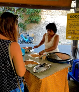 "A local specialty is ""socca,"" a flat pancake made of chickpea meal, olive oil, and spices. Super delish and not to be missed! The Marché Provençal has a regular vendor who sets up camp in the southeast corner with a portable furnace / pizza oven. The pancake is then baked via a wood fire and served off the metal pan you see here."