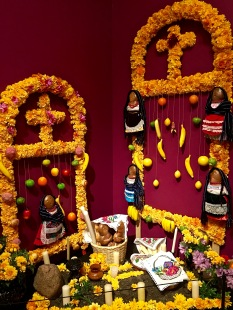 """Pictured is an ofrenda typical of people from Carapan. Men make the archway, and women decorate it with Cempasúchil, the Mexican marigold. The scent and vivid color of this flower is said to help lure the dead closer to their families. You'll can also see the corpse-shaped Pan de Muerto (""""Bread of the Dead"""") used to feed the spirits. Candles and incense are also key in creating the right atmosphere for the return of the dead."""