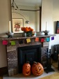 """Back at home, we created our own little ofrenda. The """"papel picado"""" (pecked paper) banner that you see here is also traditional. Patterns of skeletons, skulls, coffins, and other symbols of death are cut into tissue paper using chisels that follow a template."""
