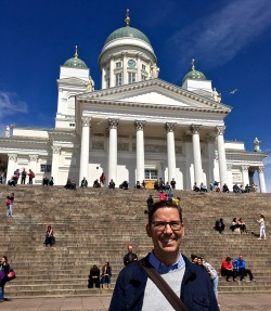 "Matthew's standing in front of ""Helsingin tuomiokirkko"" — Helsinki's Lutheran Cathedral. Yes, most Finns are Lutheran. Engel designed it (1830-1852) as a tribute to Czar Nicholas I. Intended as the cherry on Engel's Neoclassical Senate Square cake, the edifice commands a platform that overlooks the other plaza buildings. I love this pic because it communicates that issue of scale I've been talking about. Look closely, and you'll see that, like Gulliver, Matthew has Lilliputians crawling all over him."